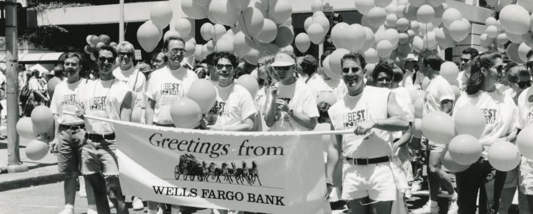 Black and white picture of a group of people carrying a Wells Fargo banner with stagecoach.