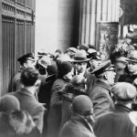 Customers line up outside a bank to withdraw their savings, but police announce that the bank is closed, 1933. Photo Credit: Library of Congress.