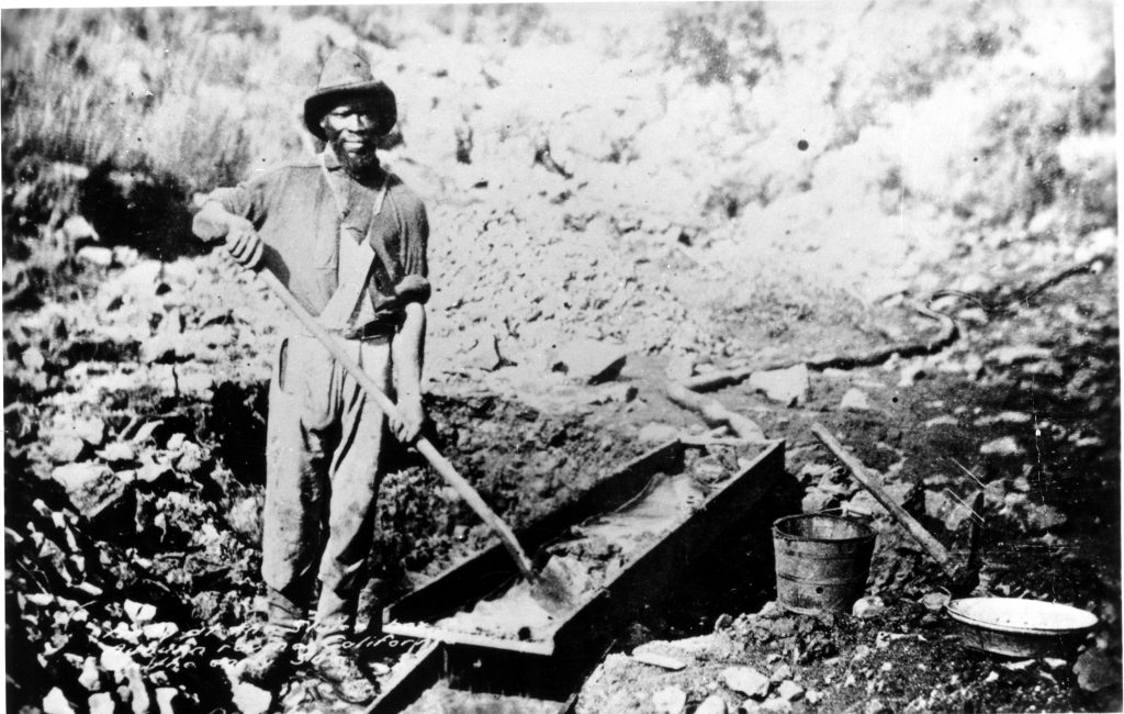 A black and white image shows a man outside holding a shovel while looking at the camera. Many large rocks are around him.