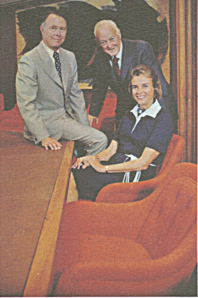 Color photograph of a woman seated in front of a board table. Behind her are two other men.