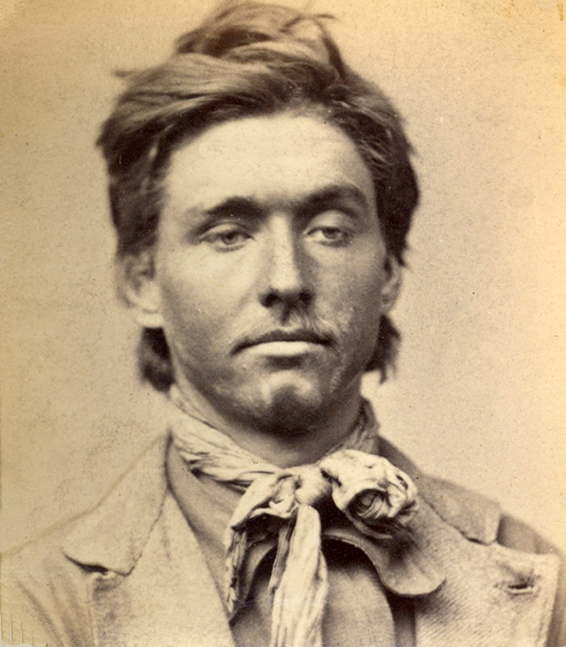 An aged photo shows the mugshot of a man who is looking down and to the left. He wears a scarf tied in a bow and a jacket.