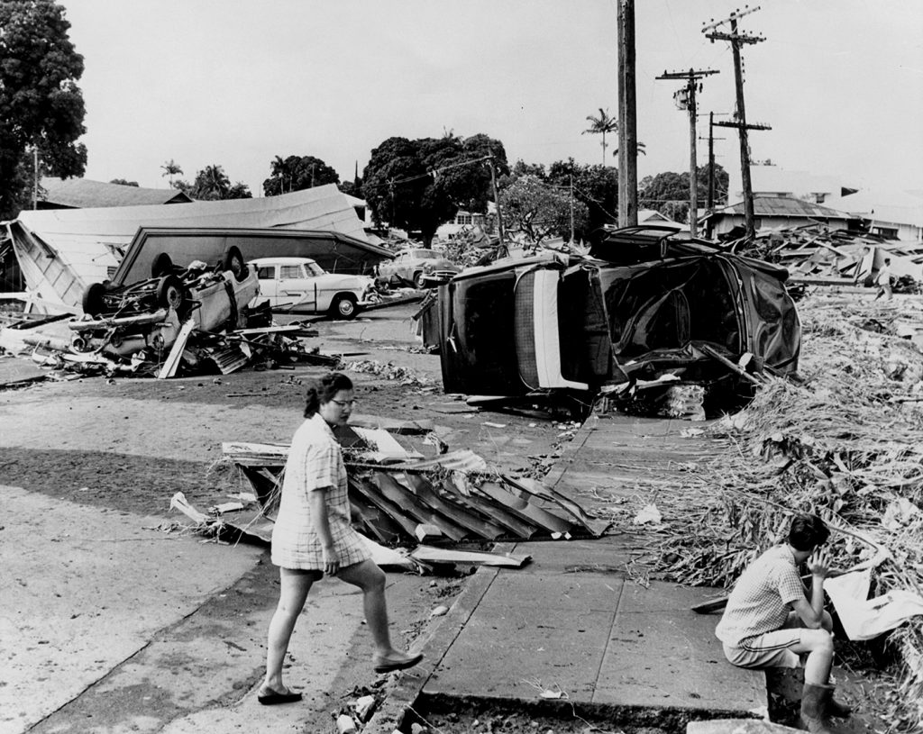 Two people rest on debris. Overturned cars and collapsed homes in the distance.