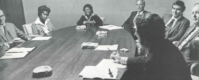 A group of men and women sit around an oval table listening while Fernando Guzman speaks.